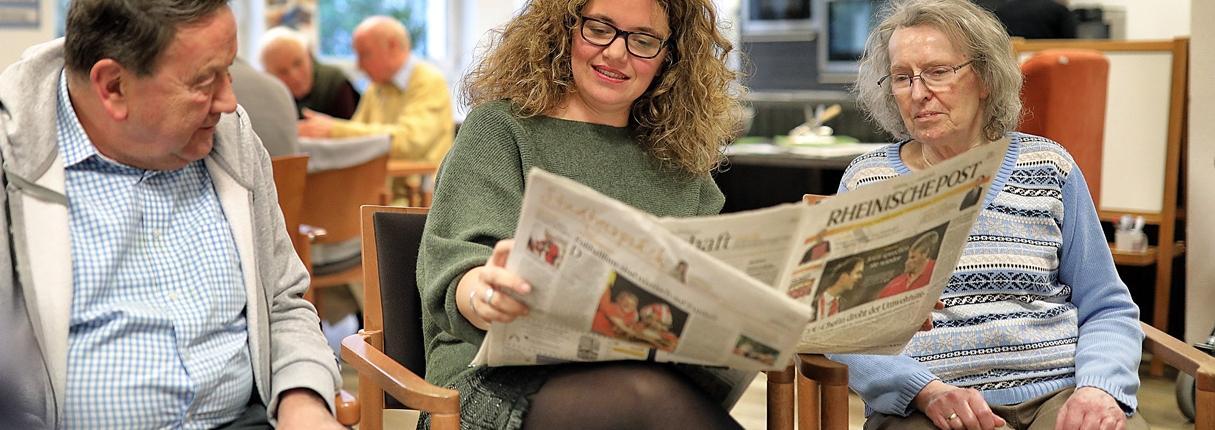 Mitarbeiterin liest aus der Tageszeitung vor