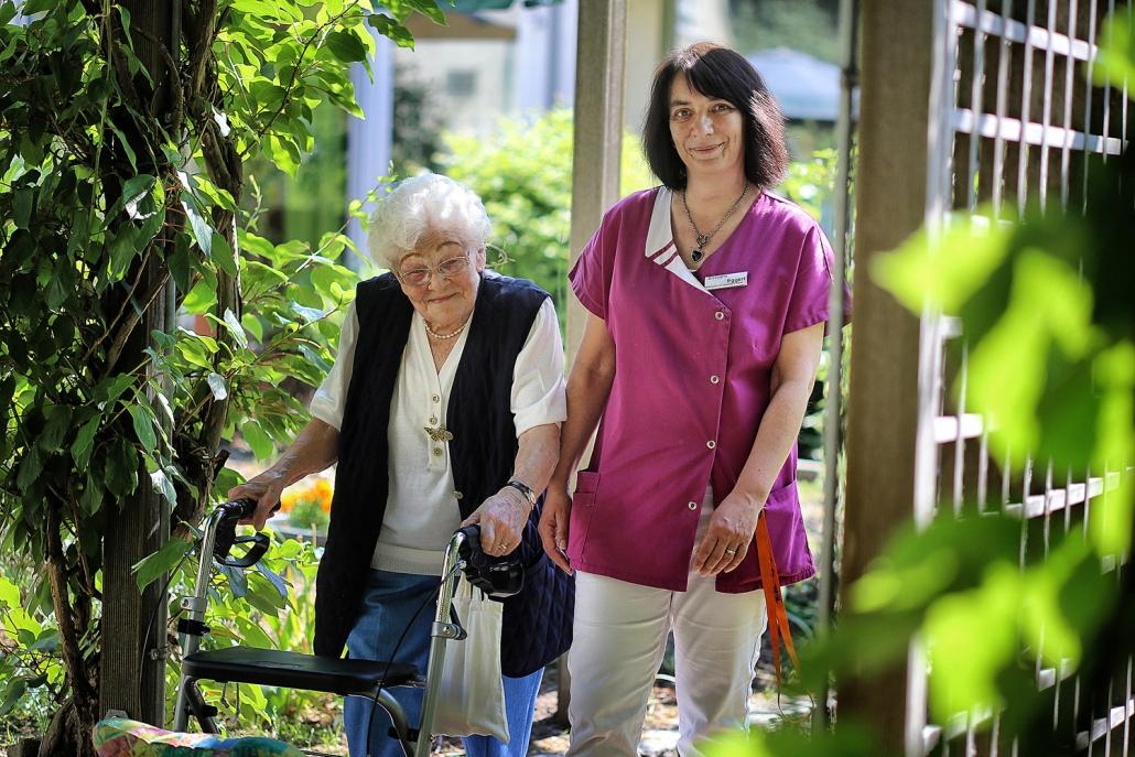 Internationaler Tag der Pflege: vl Bewohnerin Irma Blase und Sandra Eggert (Seniorenzentrum Hilden) gehen durch den Sinnesgarten